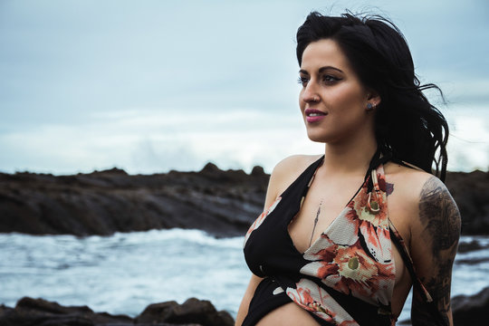 Sensual pregnant woman looking away wearing long waving lingerie robe sitting with bare belly on rocky coast in gloomy day