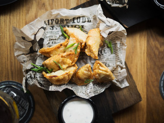 From above top view of delicious deep fried dumplings garnished with green herbs placed on paper served with white sauce on wooden table