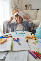 Boy with textbook on head sitting near messy table and yawning while doing homework in cozy living room during quarantine