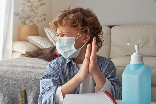 Boy in medical mask applying sanitizer on hands while sitting near sofa during quarantine at home