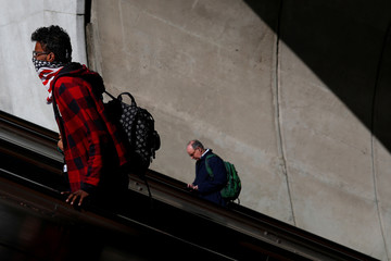 A person wearing an American flag face scarf ascends on an escalator at rail station in Washington