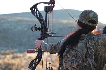 Poster de jardin Chasse Female archery hunter drawing bow