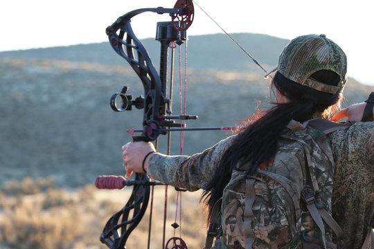 Female archery hunter drawing bow
