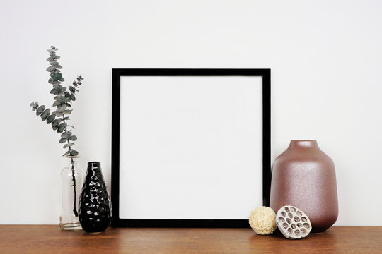Mock up black square frame with home decor and eucalyptus branch. Wooden shelf against a white wall. Copy space.