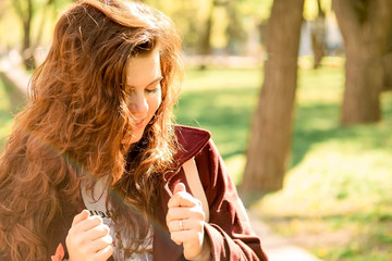 Beautiful young girl on a sunny day in a green park. Girl with curly red hair in a coat and pants.