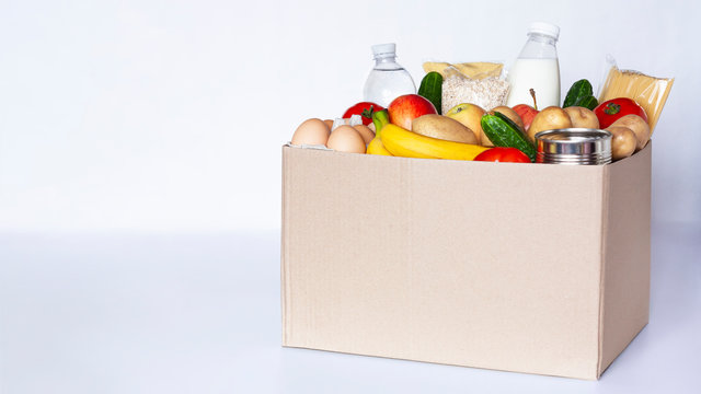 Various grocery items in cardboard box on gray table. Food box with fresh vegetables, fruits, cereals, pasta, milk, eggs and canned goods. Food delivery or donation concept. Copy space.