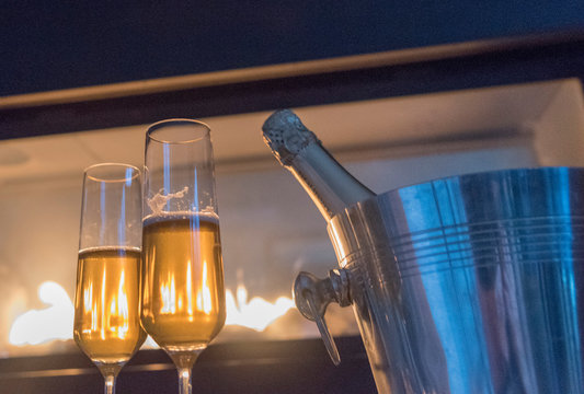 Low Angle View Of Champagne Flutes By Ice Bucket Against Burning Fireplace