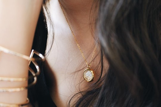 Midsection Of Woman Wearing Gold Chain With Pendant