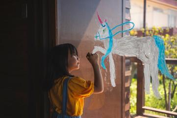 窓ガラスにユニコーンを描く女の子
