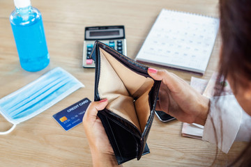 woman with financial problem during covid-19 virus pandemic hand open empty purse no money for credit card debt