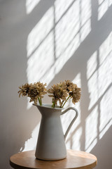 Obraz Close-up Of Flowers In Vase On Wooden Table Against Wall - fototapety do salonu