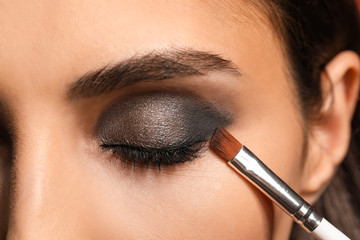 Wall Mural - Beautiful young woman applying makeup, closeup