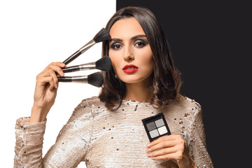 Wall Mural - Beautiful young woman with makeup brushes and cosmetics on black and white background