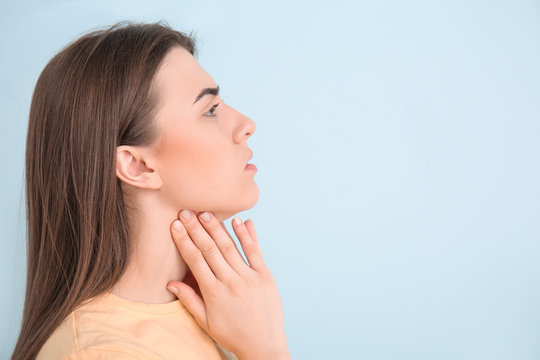 Young woman checking thyroid gland on color background