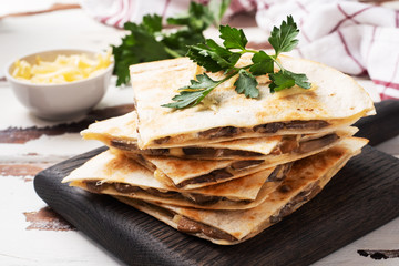Pieces of quesadilla with mushrooms sour cream and cheese on a wooden stand with parsley leaves. Wooden background copy space.