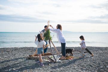 家族で協力して流木の家を作る