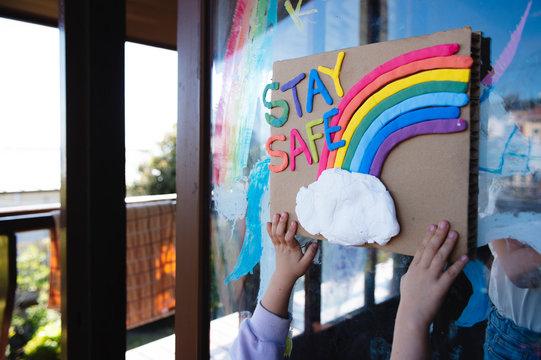 STAY SAFEの文字と虹のボードを掲げる