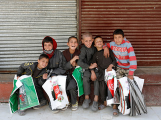 Afghan boys selling plastic bags pose for a picture at a closed food market amid the spread of the coronavirus disease (COVID-19), in Kabul, Afghanistan