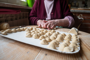 an elderly woman prepares handmade orecchiette, an excellent dish from southern Italy. orecchiette in the foreground and an old woman's hands blurred in the background