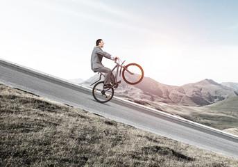 Businessman riding downhill by bike Fototapete