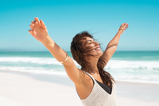 Latin carefree woman with outstretched arms at beach