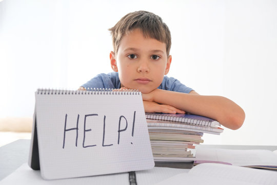 Tired sad frustrated boy sitting at the table with many books. Word Help is written on open notebook. Learning difficulties, school, education, online learning at home concept
