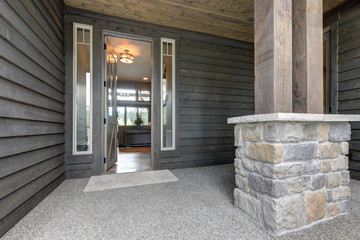 Grey new beautiful rustic home front door and entrance exterior with open door and lights on.
