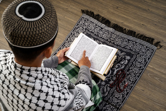 back view of muslim male reading quran