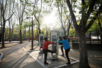 Women wearing masks to avoid the spread of the coronavirus disease (COVID-19) stretch as they work out at a park in Seoul
