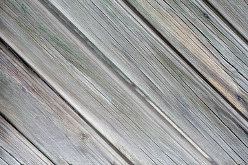 Texture of old wooden boards diagonal. Wooden gray background close-up. Dry wooden slats with burnt paint diagonal background.