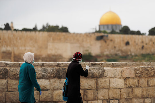 Women walk outside Jerusalem's Old City overlooking the Dome of the Rock, as Muslims mark the first Friday prayer of Ramadan amid the coronavirus disease (COVID-19) restrictions
