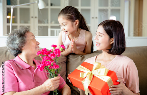 Happy mother's day  . Child and  mother congratulating grandmother  giving her flowers and  gift box