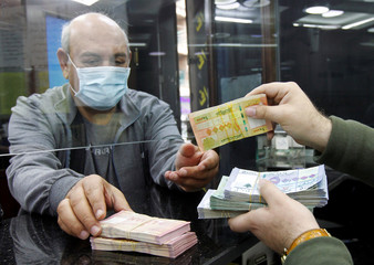 A man wearing a face mask takes Lebanese pound banknotes at a currency exchange shop in Beirut