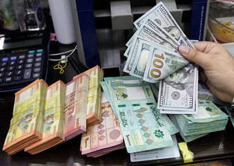 A man counts U.S. dollar banknotes next to Lebanese pounds at a currency exchange shop in Beirut