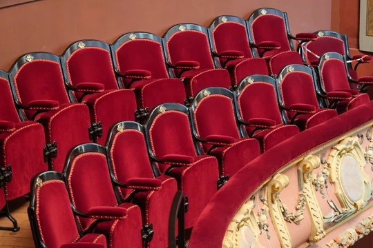 Balcon de théâtre, avec deux rangées de fauteuils rouges dans une salle de spectacle vide
