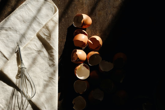 High Angle View Of Eggshell With Wire Whisk On Table