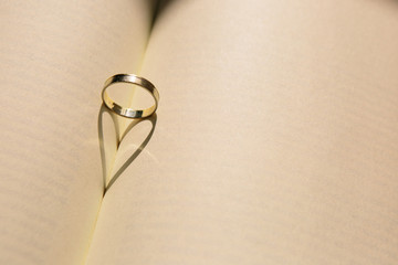 Gold wedding ring forming a heart with the shadow on an old book with yellowed pages. Old picture. Copy space
