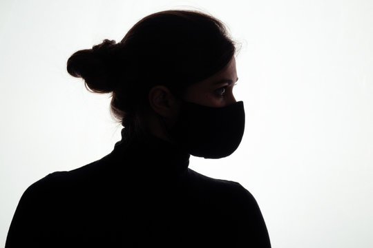 silhouette of confident young woman in protective mask on studio background, girl looking straight readynto deal with danger, concept health and safety