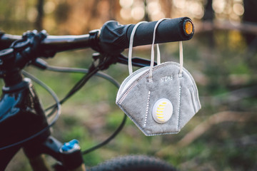 face mask, with filter pm 2.5. Flu epidemic, dust allergy, protection against virus. Covid 19 virus concept. A carbon filter respirator hangs on the handlebars of a bicycle in a forest
