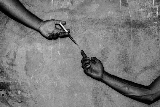 Close-up Of Hand Passing Syringe
