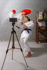 A little girl in kimono is engaged in online karate training on a mobile device with an imaginary opponent who is trying to hit through the screen.