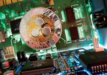 Representation of the virtual currency Ripple coin is seen on a motherboard in this picture illustration