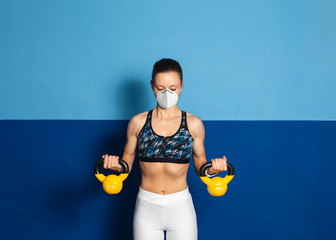 Young fit woman with n96 face mask  doing biceps exersice at the gym with kettlebells. Fitness strength workout under coronavirus health crisis.