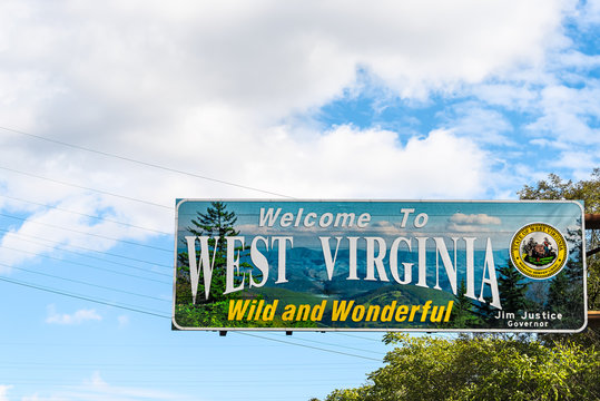 Kenova, USA - October 17, 2019: Welcome to West Virginia sign Wild and Wonderful with mountains picture and blue sky by Kentucky border