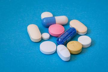 Fototapeta Kolorowe tabletki na niebieskim tle. obraz