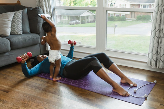 Woman working out at home with baby during quarantine
