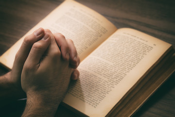 Hands clasped in prayer over a Holy Bible, wooden table background.