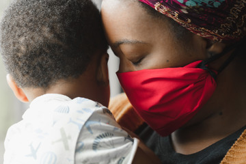 Mom embraces toddler through pandemic mask