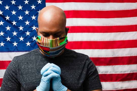Black man wearing cloth mask praying for hope in front of patriotic of American flag