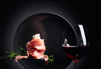 Fototapete - Glass of red wine and prosciutto or spanish jamon with rosemary.